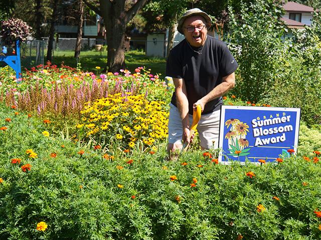 man smiling in his summer blossom award winning garden