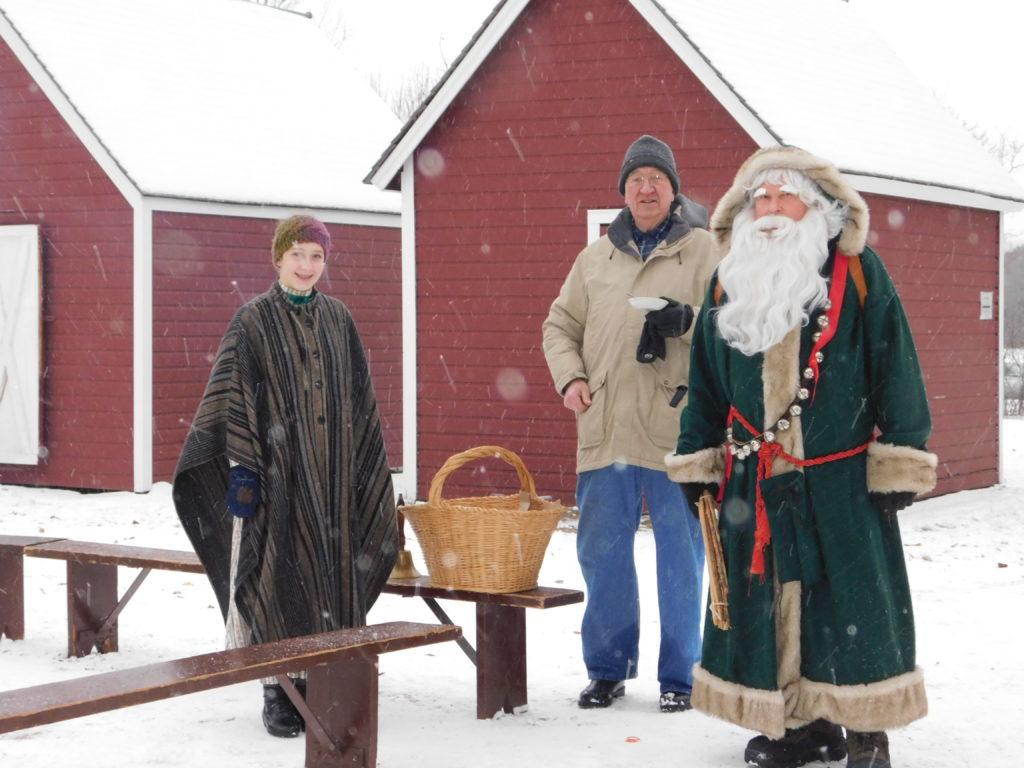 Santa and children standing in front of snowy barn