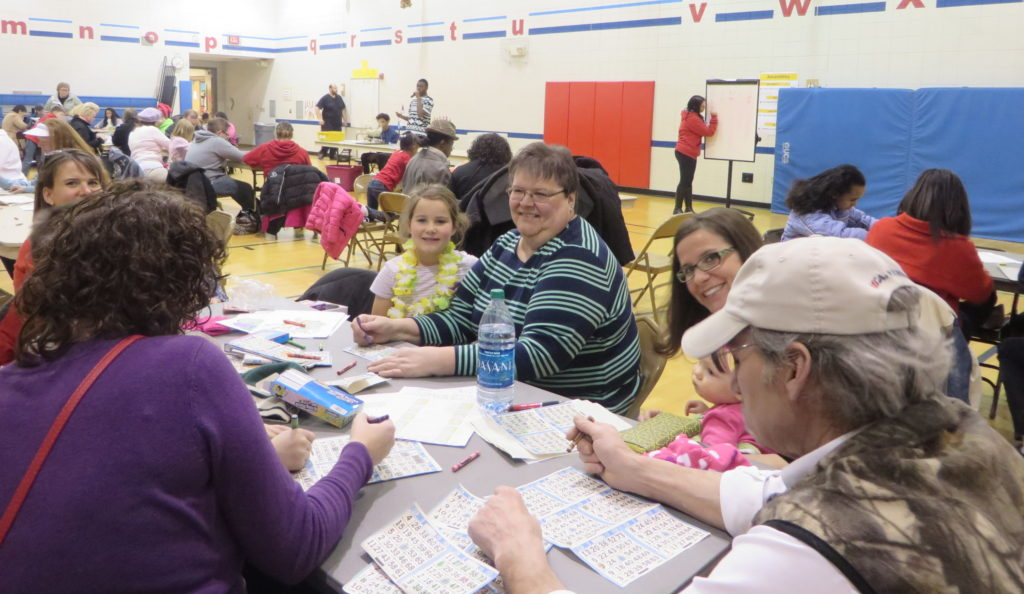 Family playing BINGO in a gym