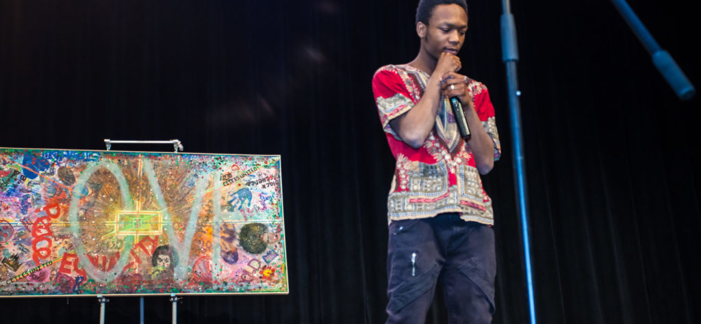 Youth speaking in front of art