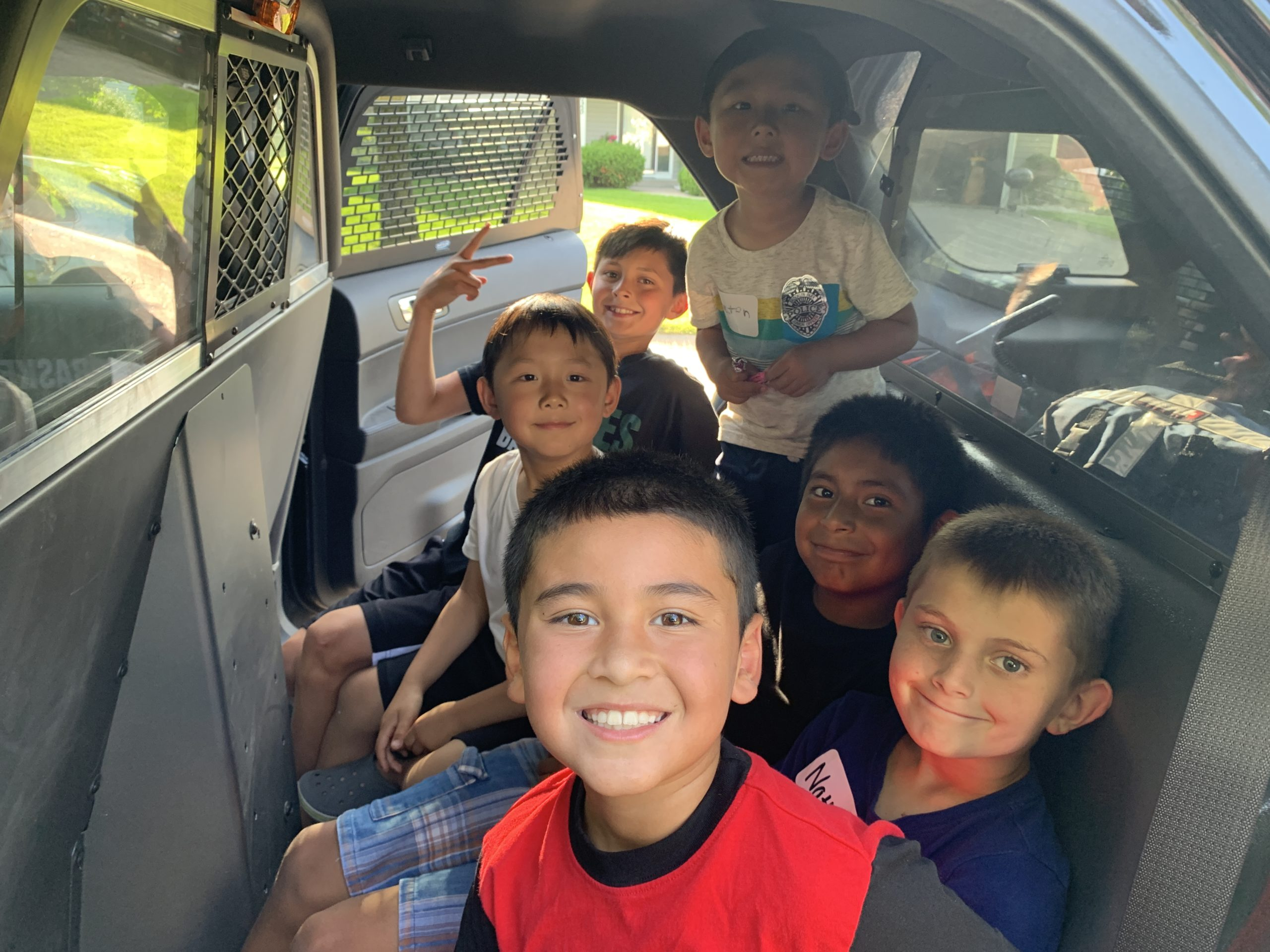 kids in the back of a police car smiling