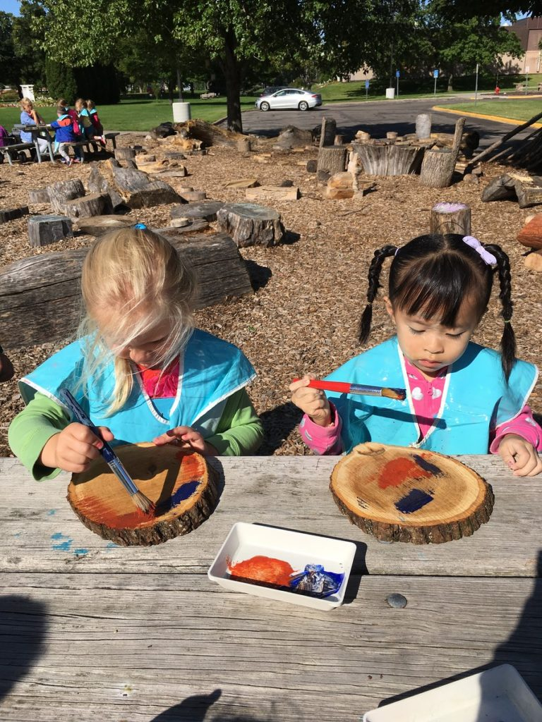 Two girls painting wooden circles cut from trees
