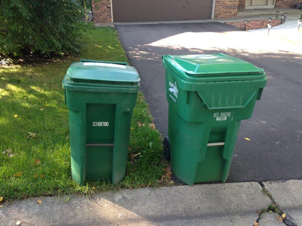 Two green garbage bins near the sidewalk.