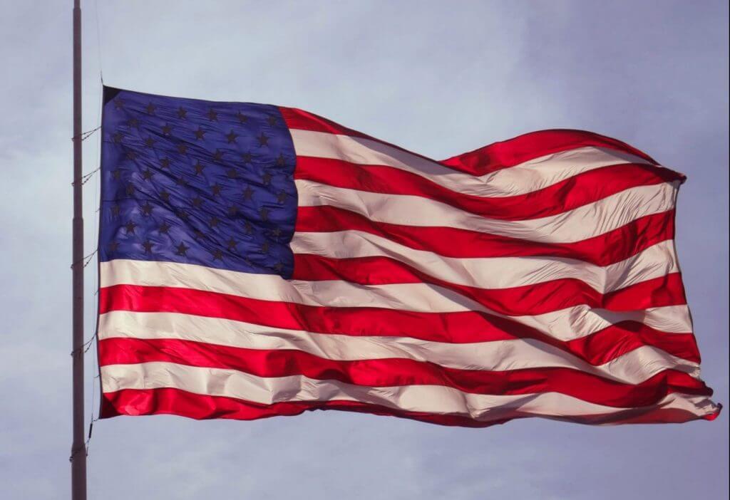 american flag waving at half staff