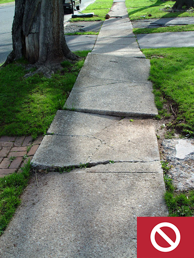 This sidewalk is cracked and uneven, which is a safety hazard.
